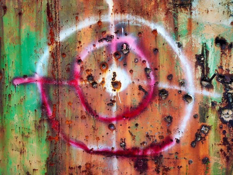 Insecurity Security In Politics And Policy - Green Agenda - Image of Gunshots and a target on a rusty wall
